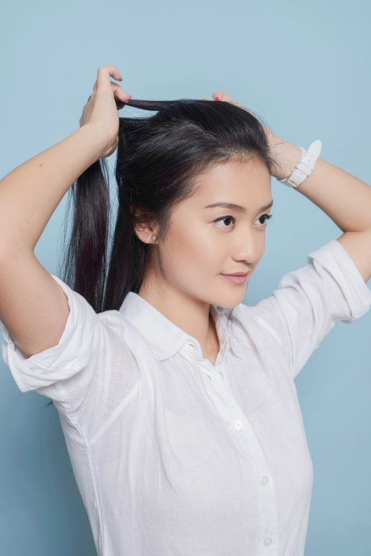 Fishtail French braid: Asian woman starting to braid her long black hair wearing a white blouse