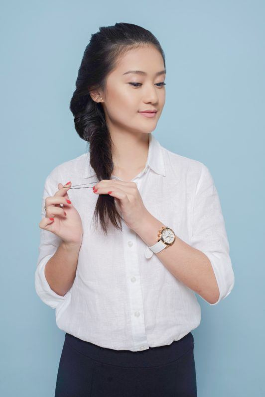Fishtail French braid: Asian woman tying her long black hair in fishtail French braid wearing a white blouse and black skirt