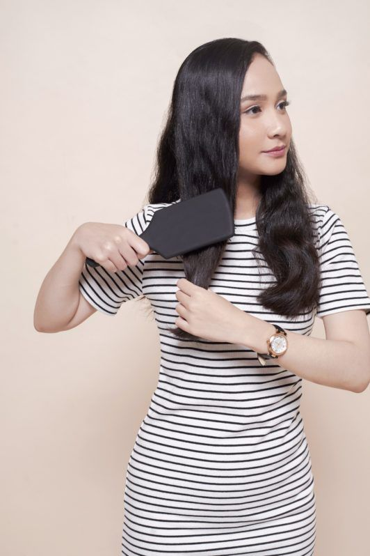 How to use a flat iron: Asian woman brushing her long black wavy hair wearing a striped dress
