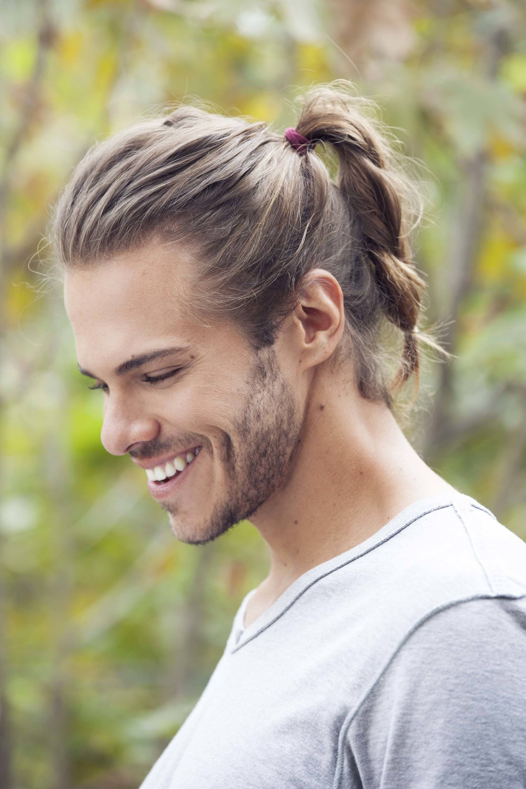 Men's grooming:: Closeup shot of a man with dark brown hair in a ponytail braid