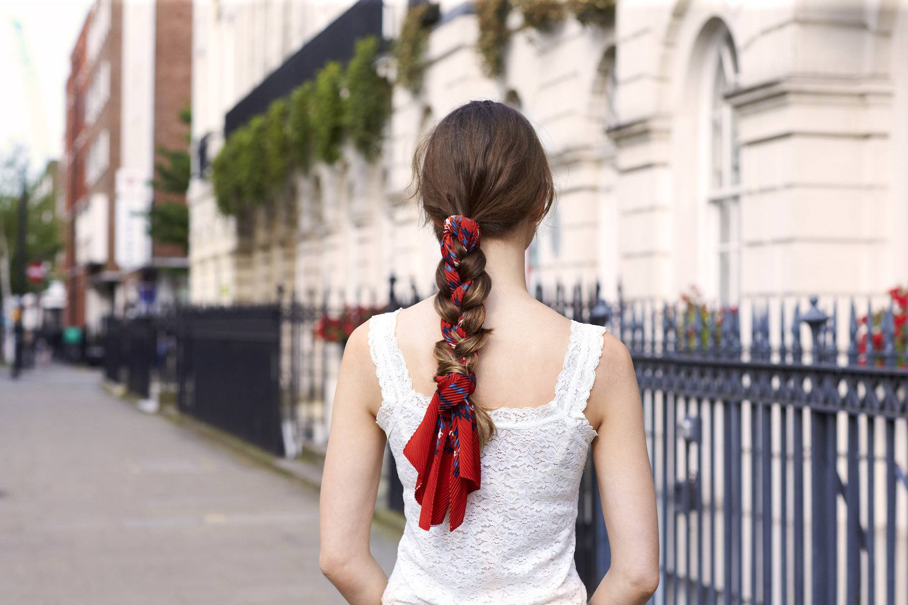 Casual hairstyle: Back shot of a woman with long dark brown hair in scarf braid wearing a white top outdoors