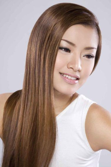 Brown hair color: Asian woman with long straight brown hair wearing a white sleeveless shirt