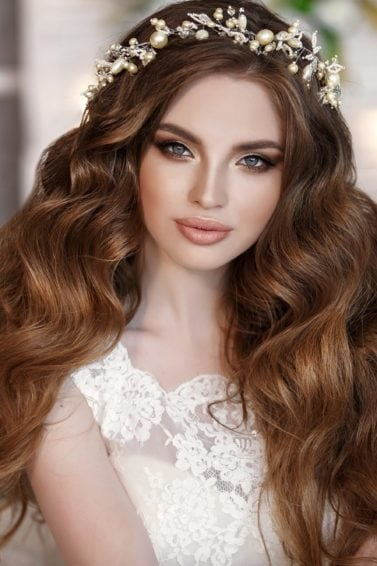Curly wedding hairstyles: Woman with long brown curly hair wearing a wedding dress and flower crown