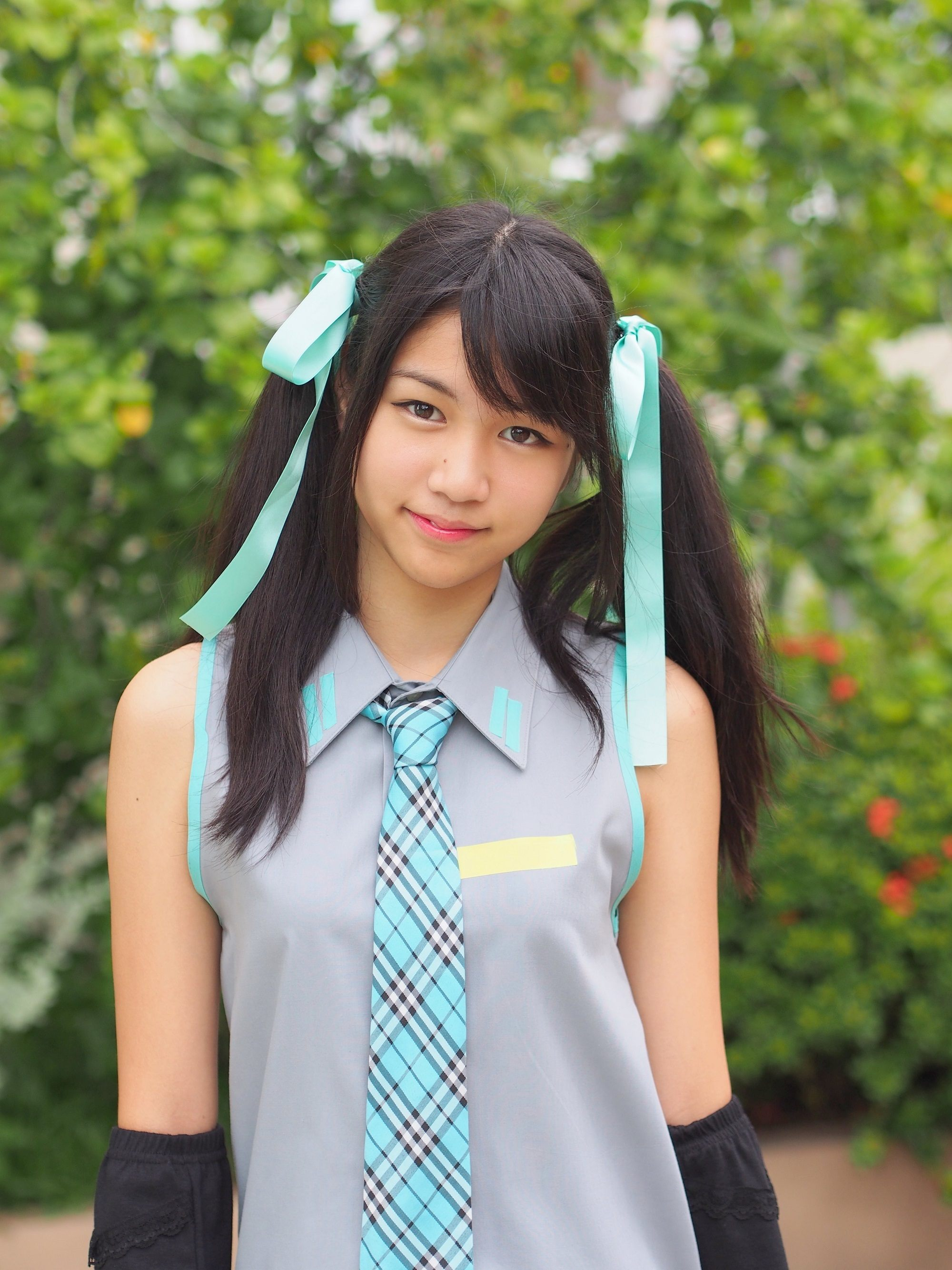 Kawaii hairstyles: Girl with long black hair in pigtails wearing a sleeveless polo with necktie