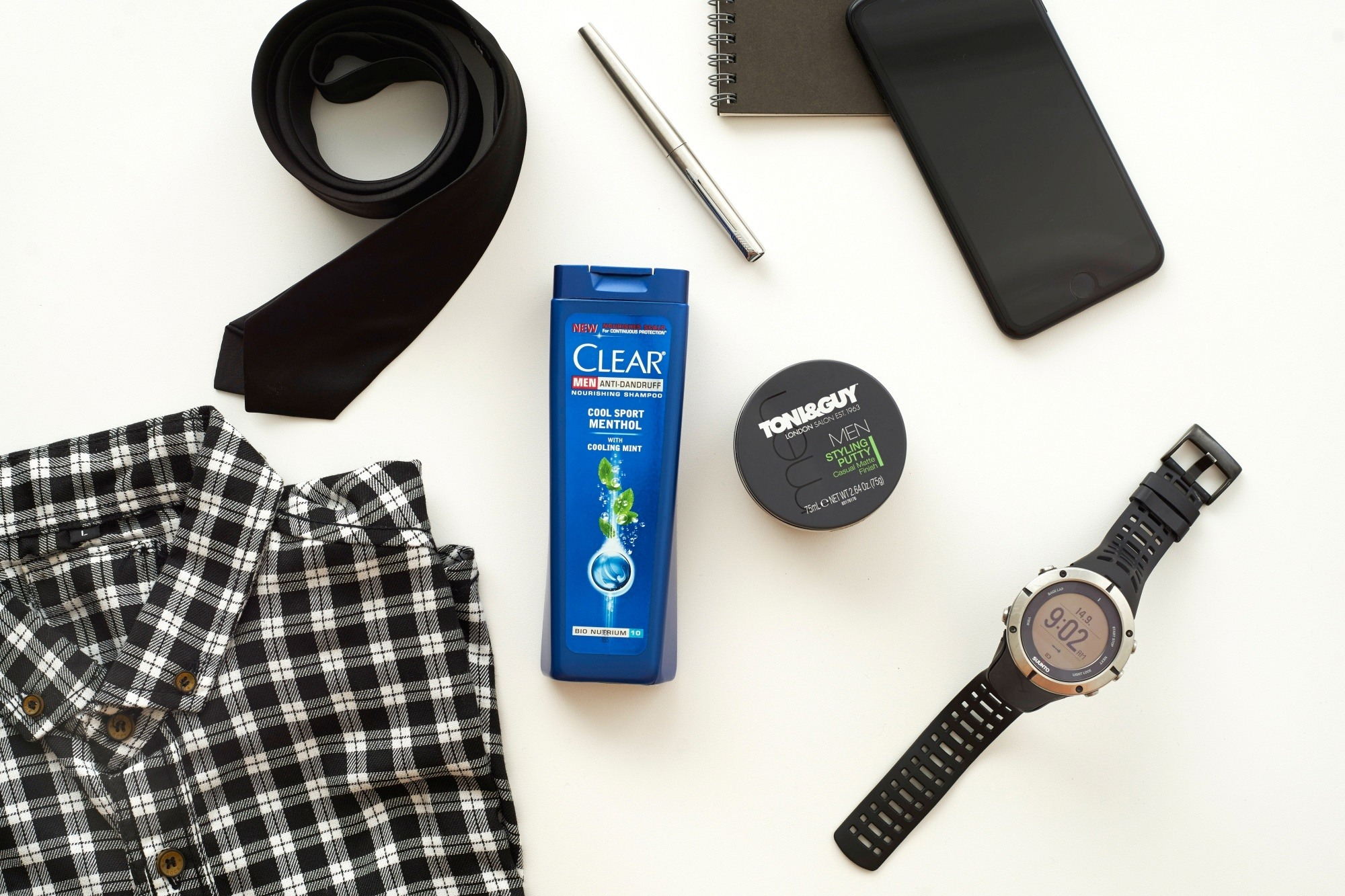 Men's grooming habits: Flatlay of men's shampoo and styling wax and men's clothes and accessories