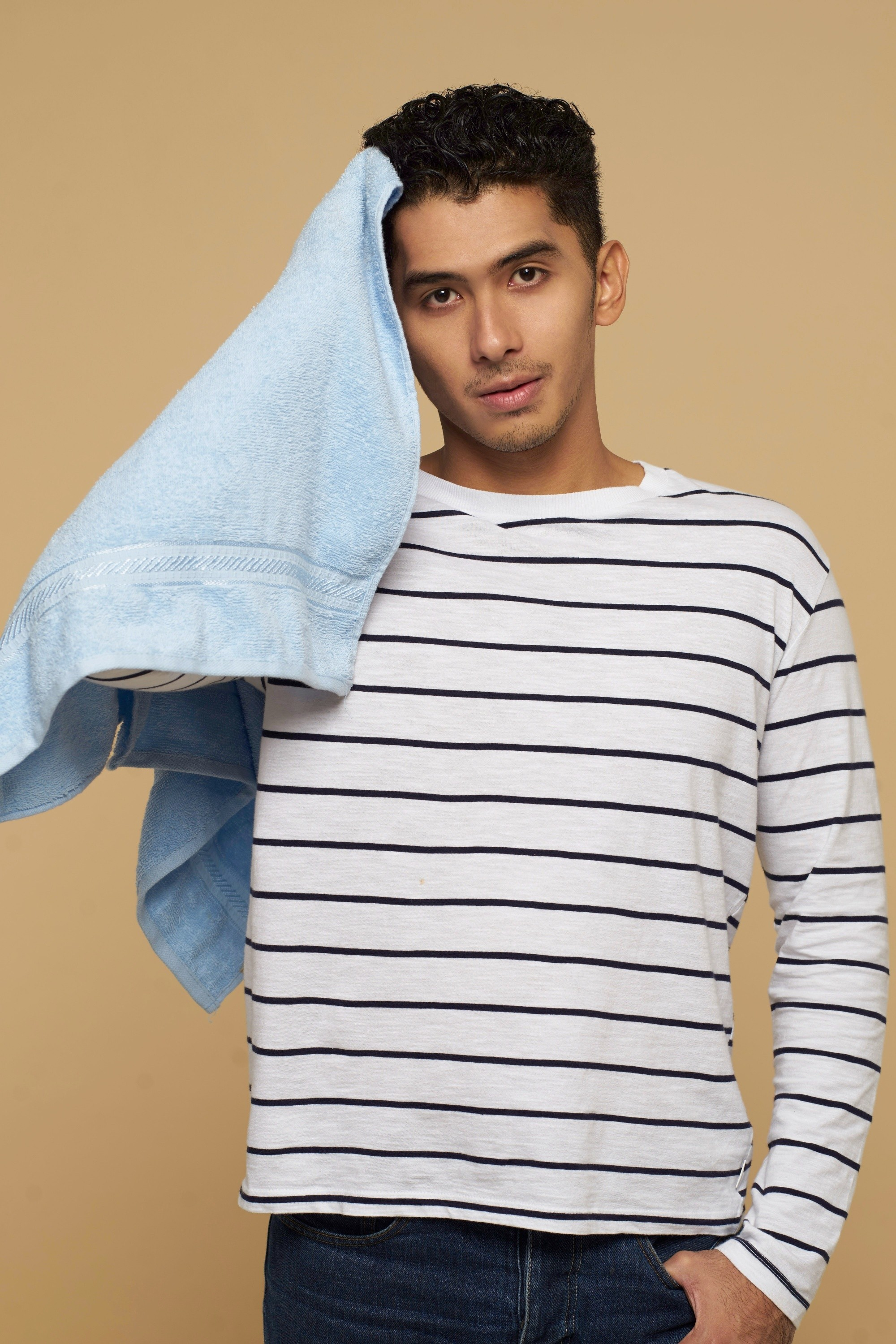 Men's grooming: Asian man holding a blue towel and patting his short black hair dry