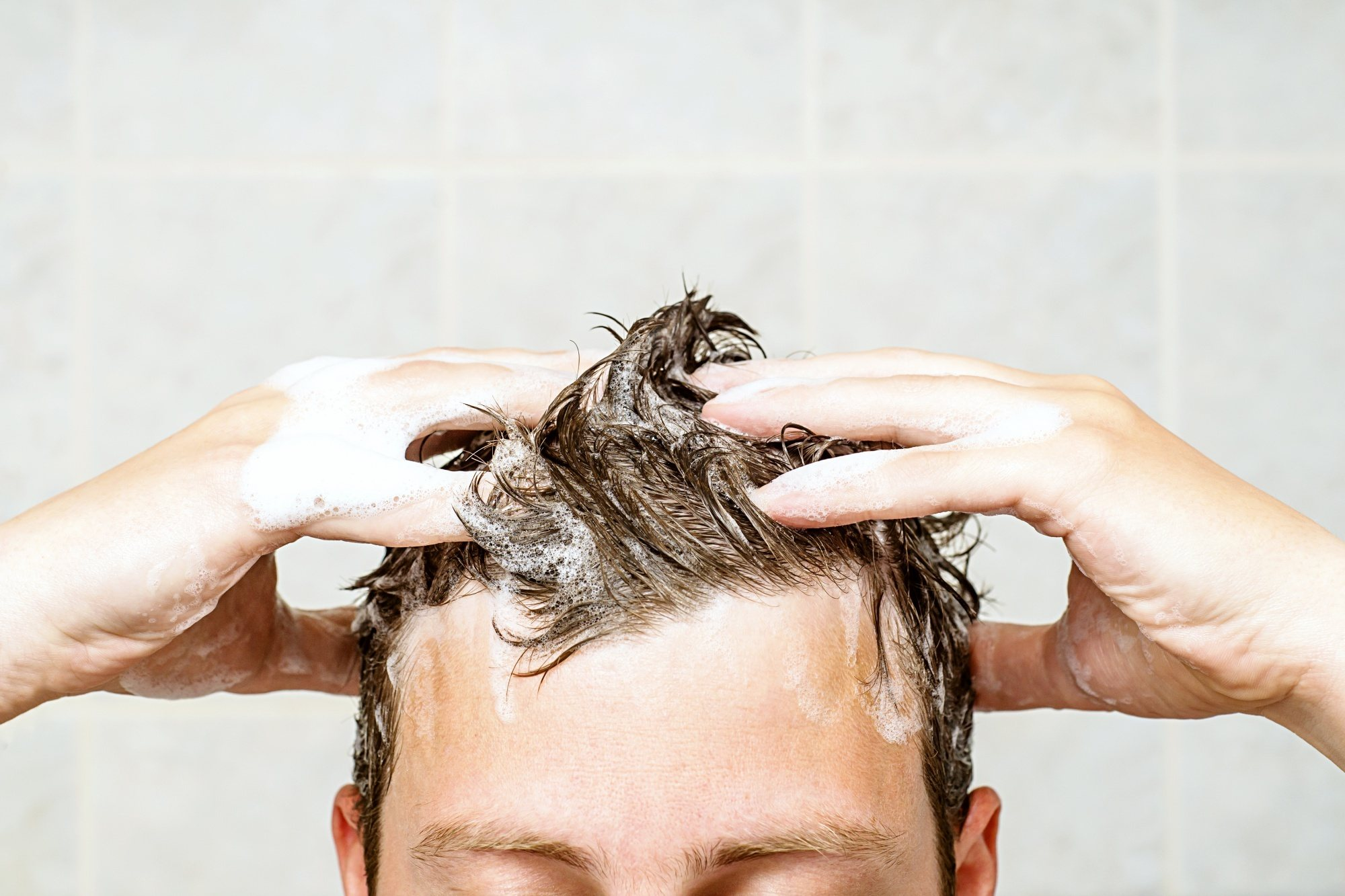 Men's grooming: Closeup shot of a man washing his short brown hair