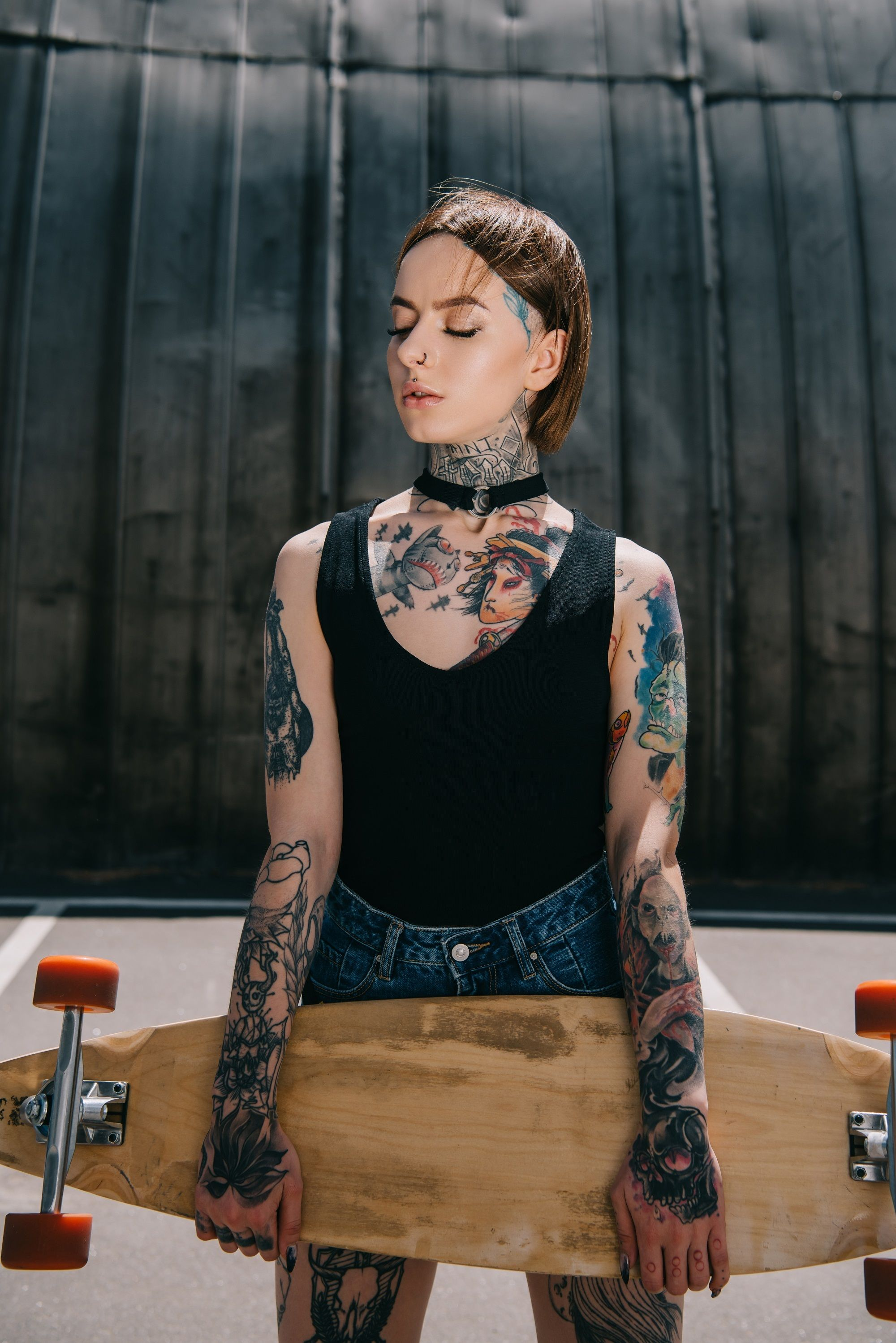Hairstyles for skaters: Woman with slicked back bob and tattoos holding a skateboard