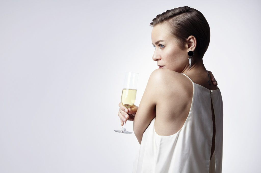Party hairstyles for short hair: Woman with pixie cut holding a champagne glass