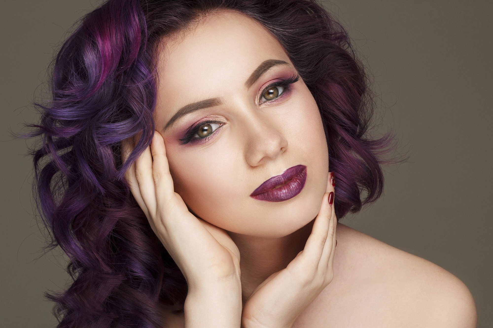 Purple hair idea: Woman with curly hair and eggplant highlights