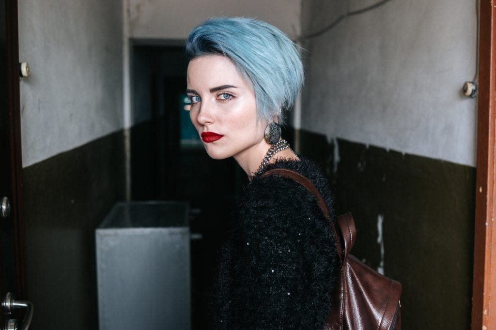 Blue hair: Woman with pale skin and short ice blue hair