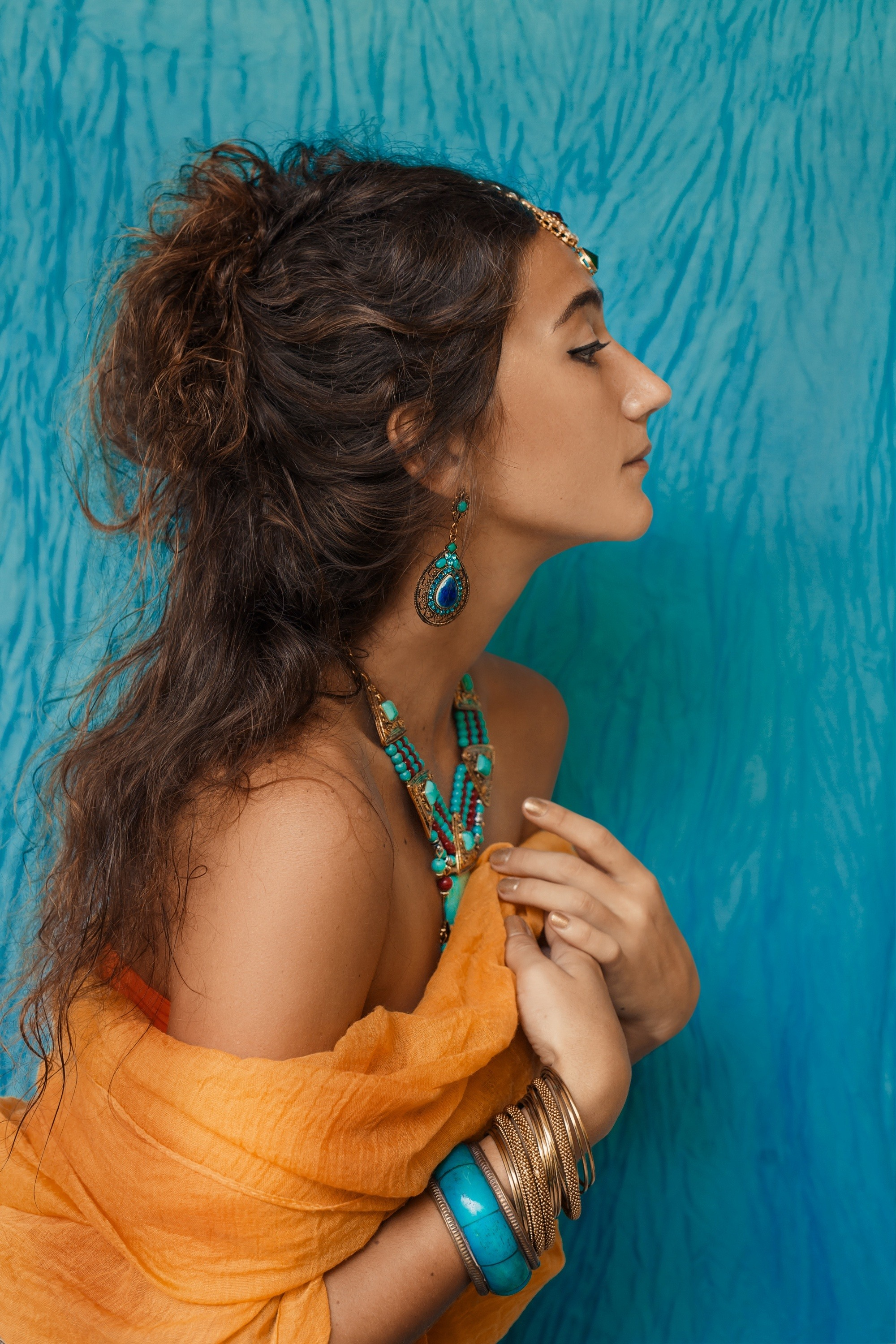 Boho hairstyles: Side view of a woman with long dark curly hair wearing an off-shoulder dress