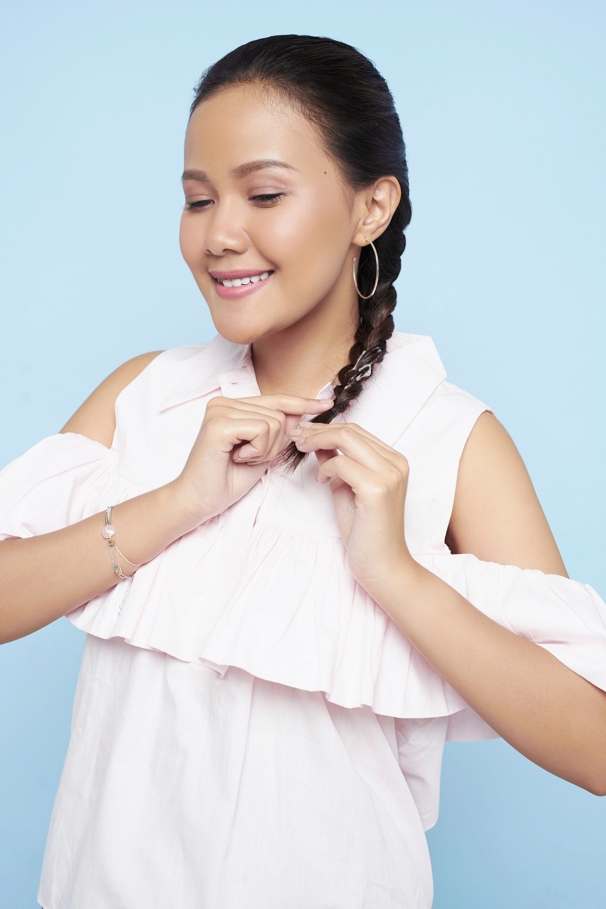 Easy braids for long hair: Asian woman putting hair in Dutch braid