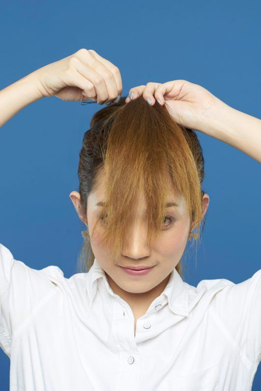 Asian woman putting faux bangs in bobby pin