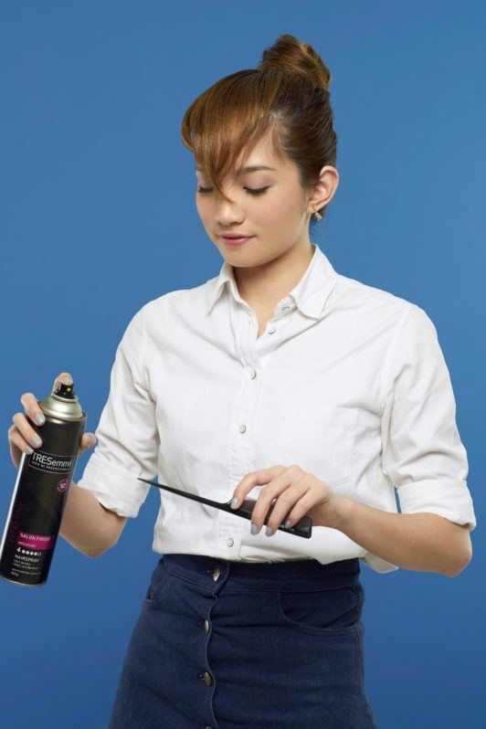 Making faux bangs 6: Asian woman spritzing hairspray on tail comb