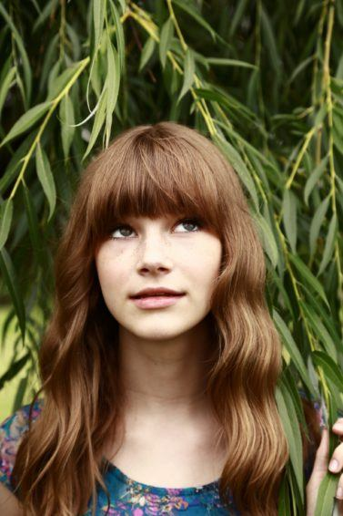 Short straight hairstyles: Woman with long brown wavy hair and bangs