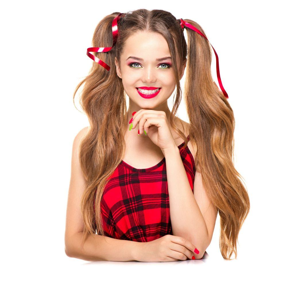 Anime hairstyles: Girl with long brown hair in high pigtails wearing a red plaid sleeveless shirt and standing against a white background