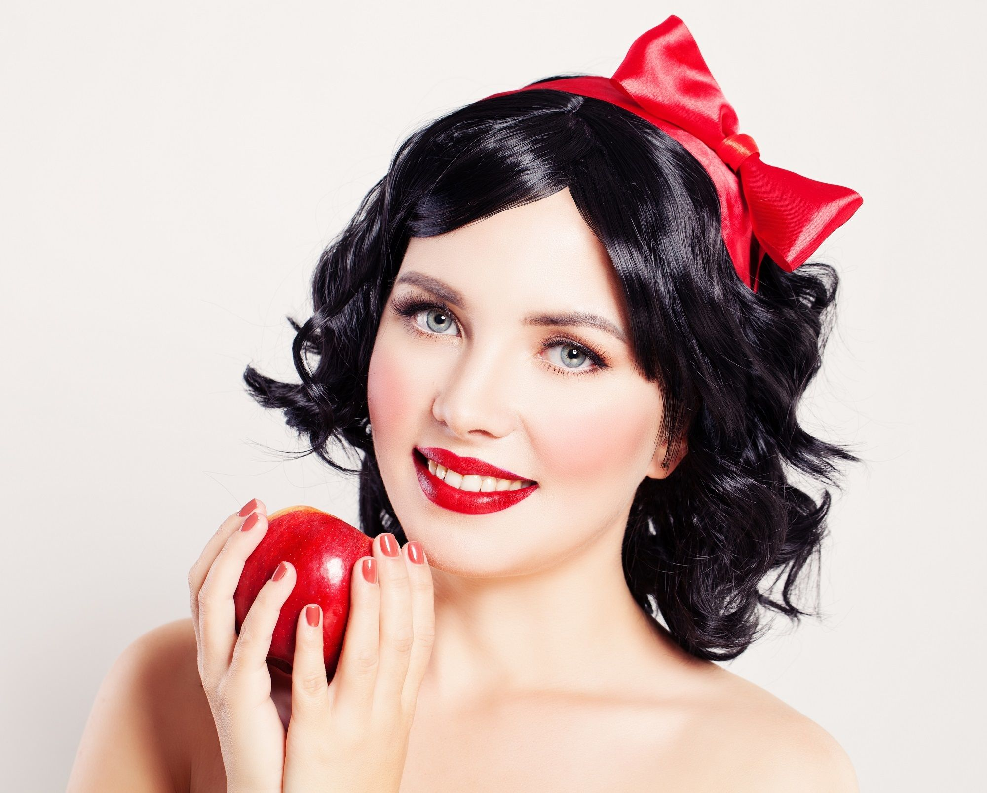 Anime hairstyles: Closeup shot of woman with short curly black hair and red ribbon on hair holding an apple