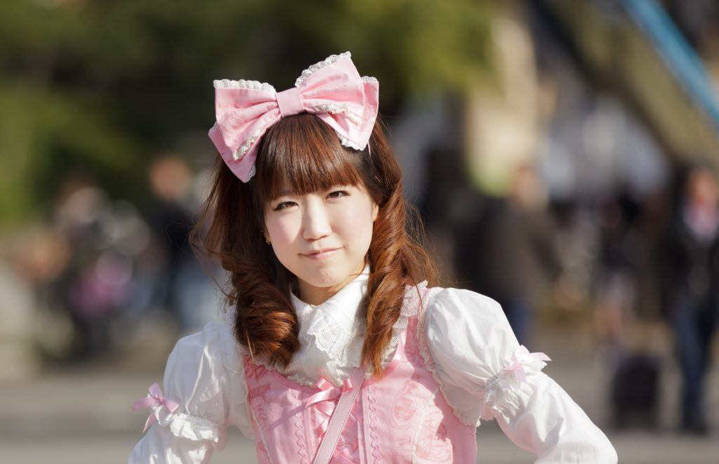 Anime hairstyles: Asian woman in outdoor location wearing white long-sleeved blouse and pink pinafore and huge pink bow on brown curly hair