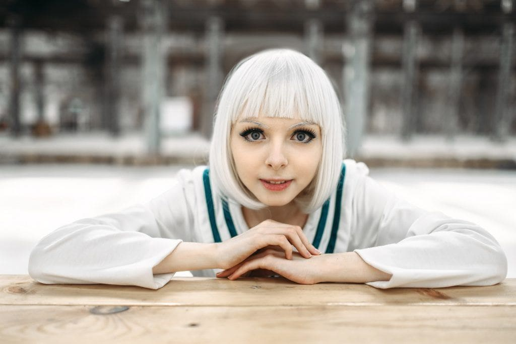 Anime hairstyles: Closeup shot of girl with short ice blonde hair with bangs wearing Japanese schoolgirl uniform leaning on wooden table