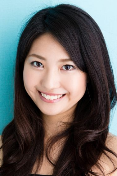 Best haircuts for long hair: Asian woman with long black wavy hair close up shot against a blue background