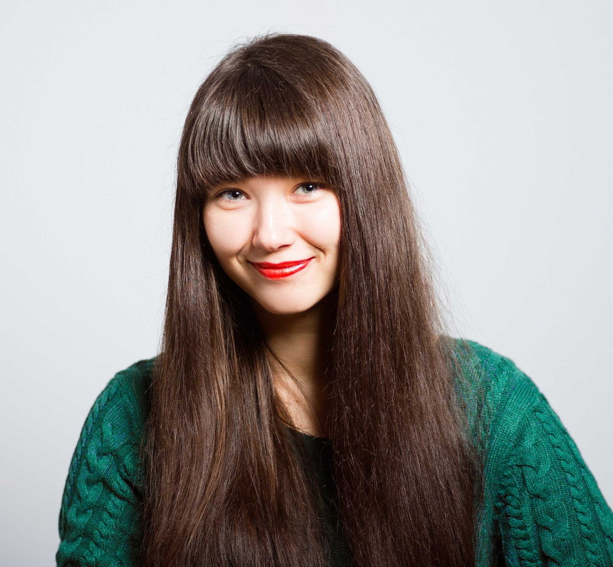 Best haircuts for long hair: Woman wearing a green sweater and long straight dark brown hair with full bangs standing against white background