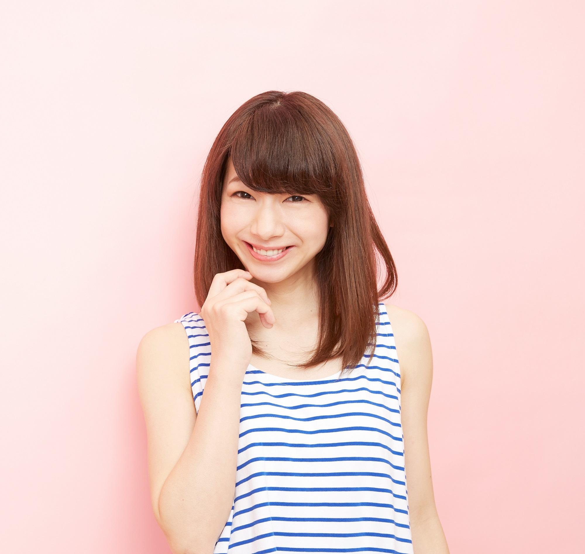 Best haircuts for long hair: Asian girl wearing a striped sleeveless shirt with shoulder-length hair with bangs standing against a pink background