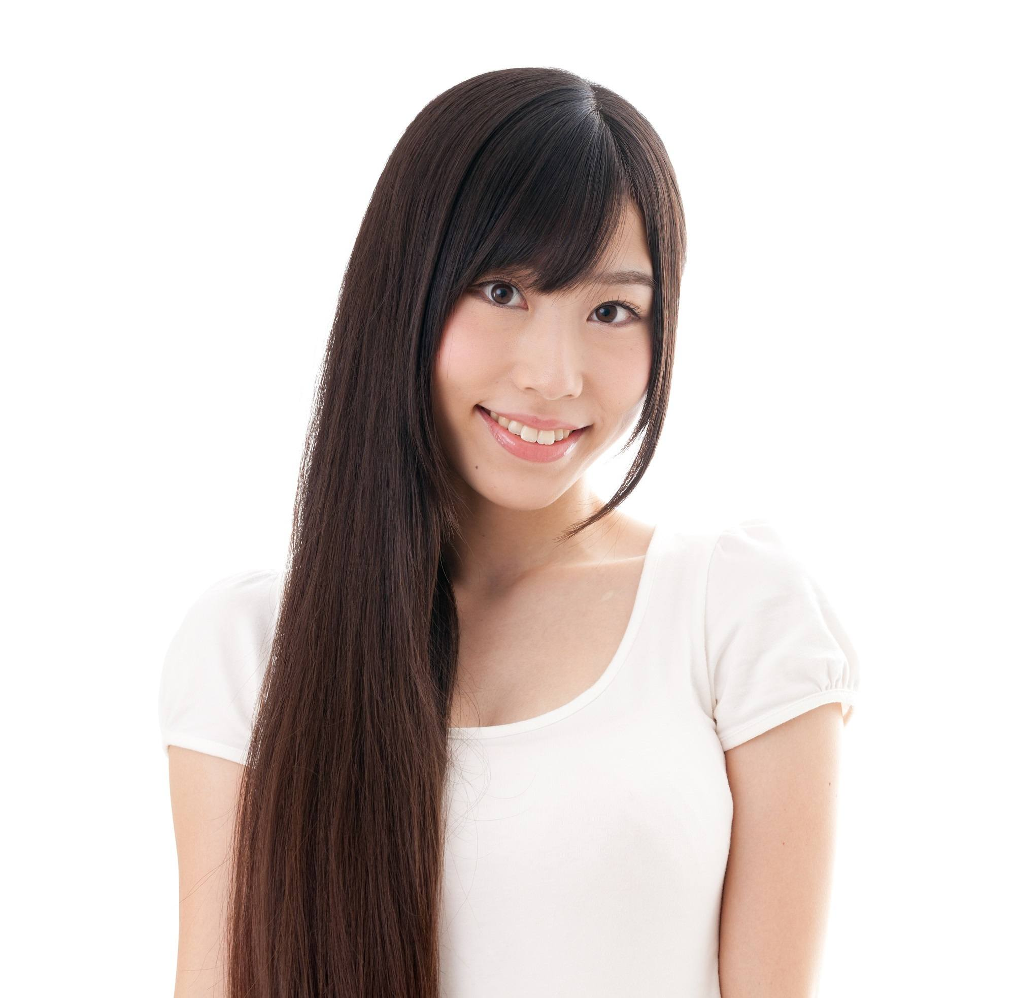 Best haircuts for long hair: Asian woman wearing a white shirt with long straight black hair and curtain bangs against while background