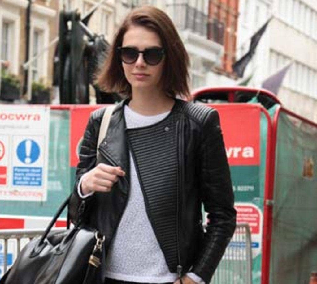 Blunt haircut: Woman with brown blunt lob wearing shades and black leather jacket walking on a street