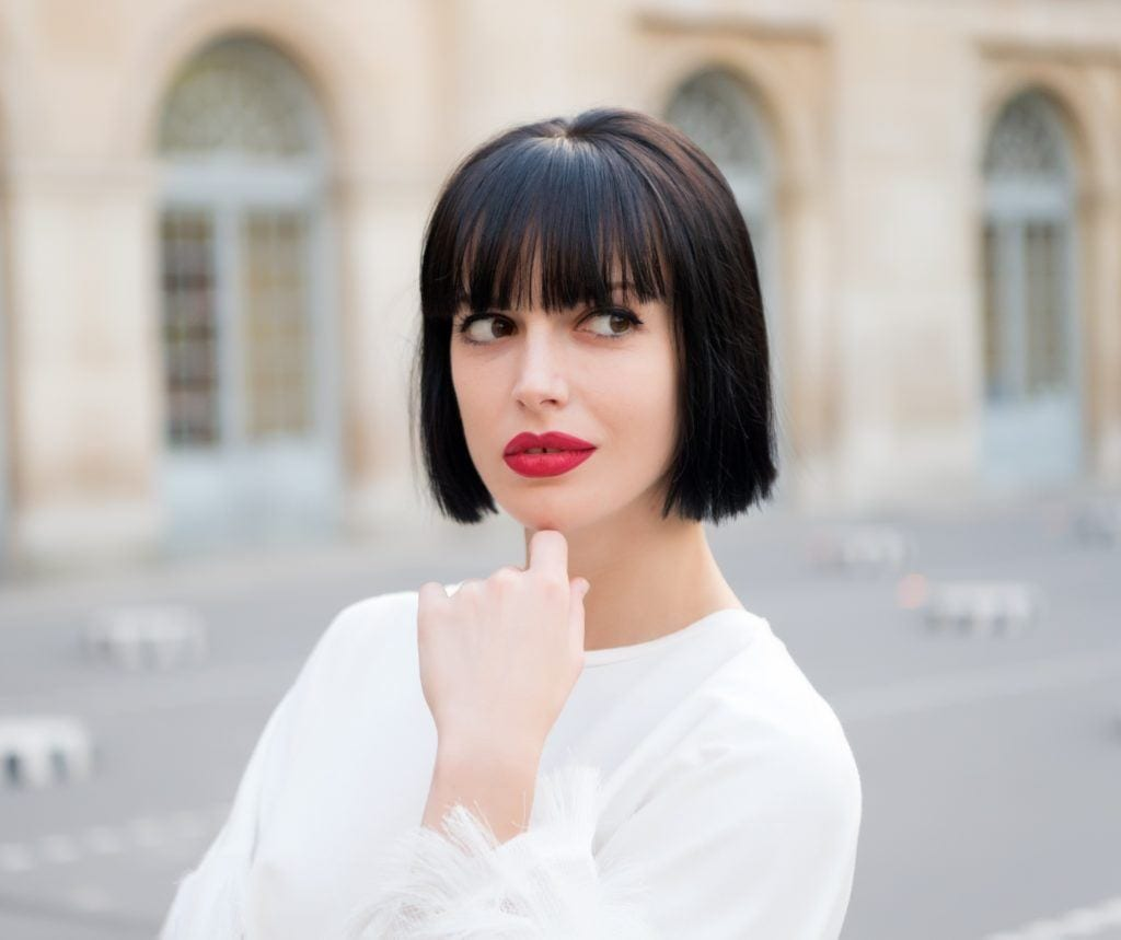 Blunt haircut: Woman on the street wearing white long-sleeved shirt with black short hair and bangs