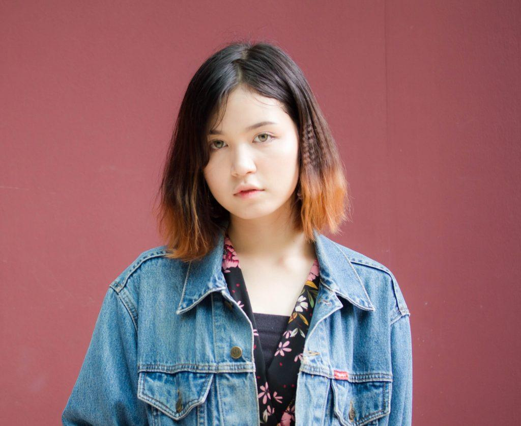 Blunt haircut: Girl wearing a denim jacket with blunt bob dip dyed brown standing against a burgundy background