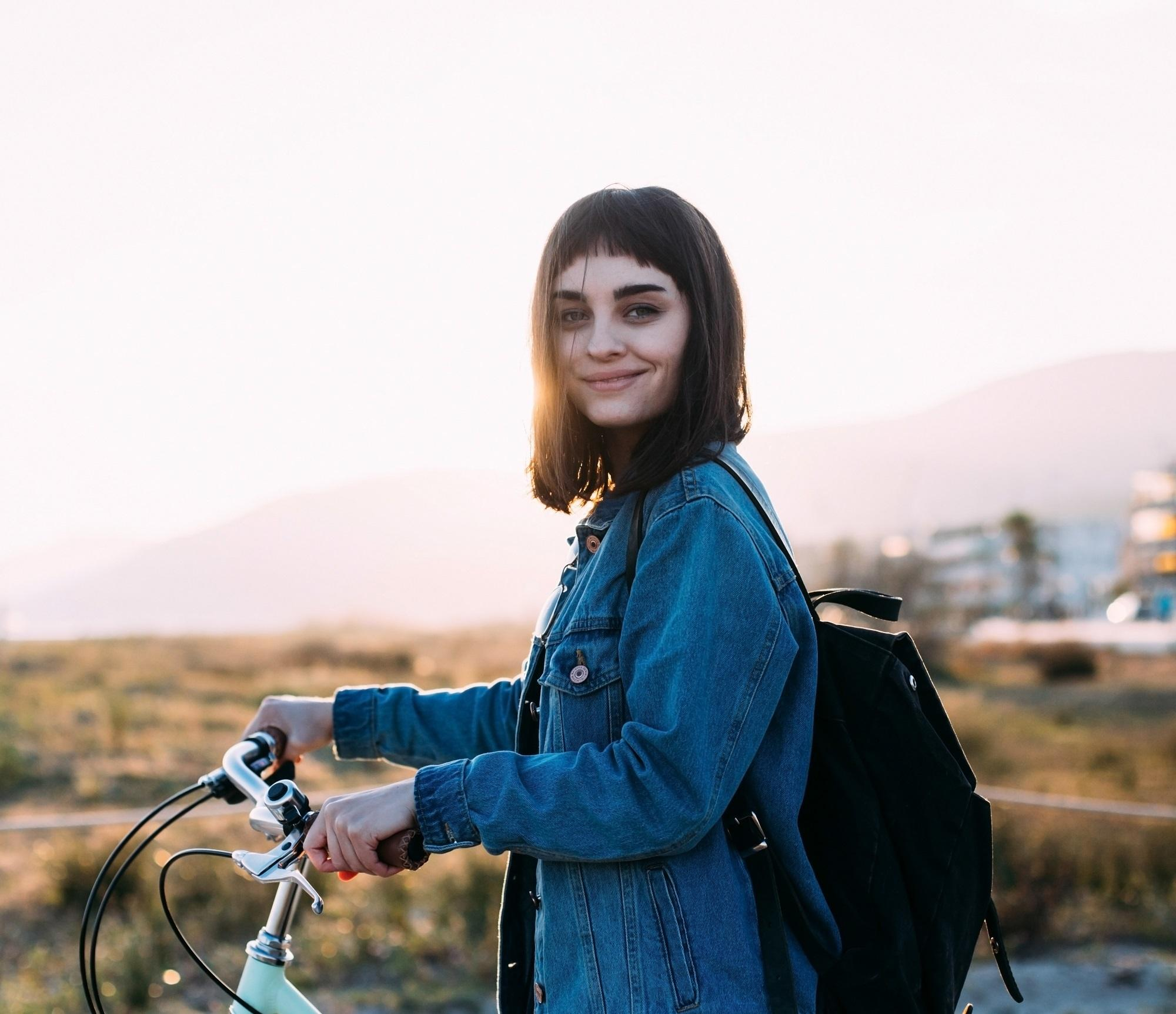 Blunt haircut: Girl with black lob and baby bangs wearing a denim jacket standing next to a bike outdoors