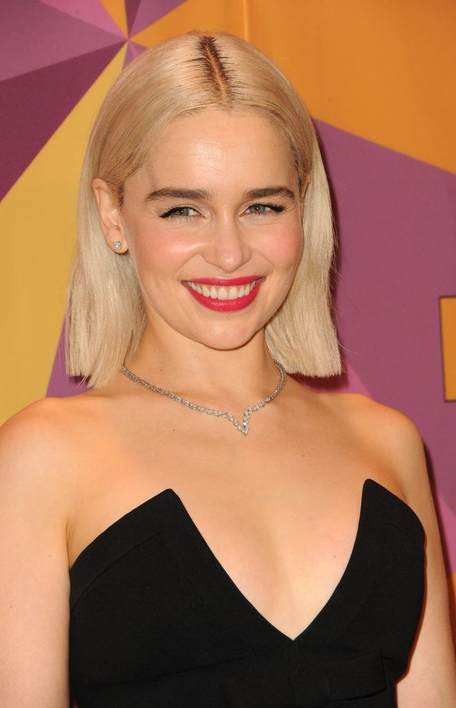 Celebrity short hair: Actress Emilia Clarke woman with straight blonde hair in long bob haircut wearing a low-cut black dress standing against a multi-colored background