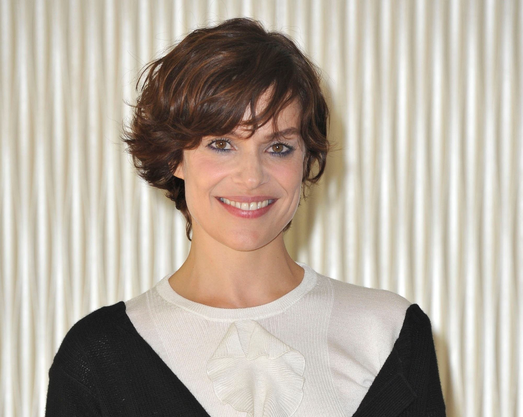 Celebrity short hair: Italian actress Micaela Ramazzotti woman with short brown hair with short waves standing against a cream-colored background