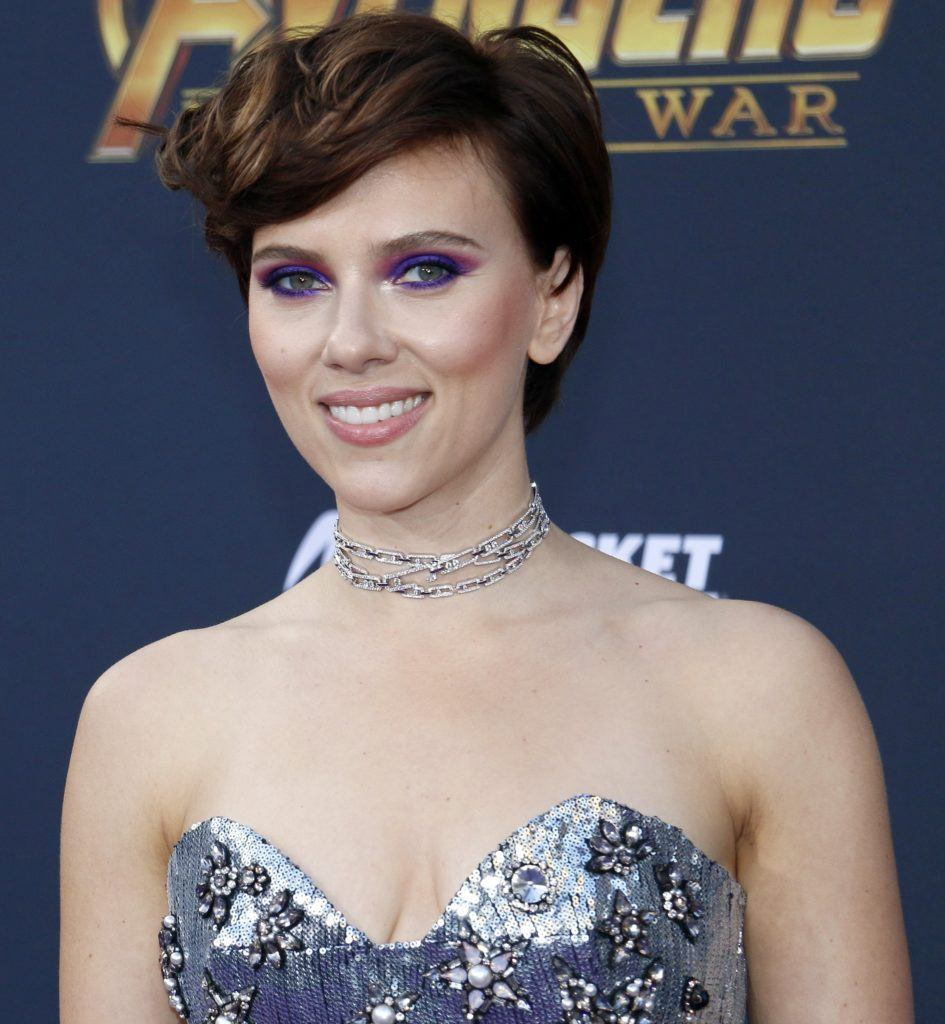 Celebrity short hair: Actress Scarlett Johansson woman with dark brown hair in pixie cut with long wavy bangs wearing a silver formal dress standing against a dark blue background