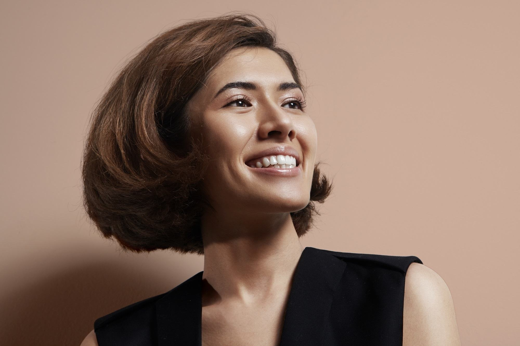 Chin length hairstyles: Closeup shot of a woman wearing black sleeveless shirt with short brown hair in chin length bouncy bob against brown background