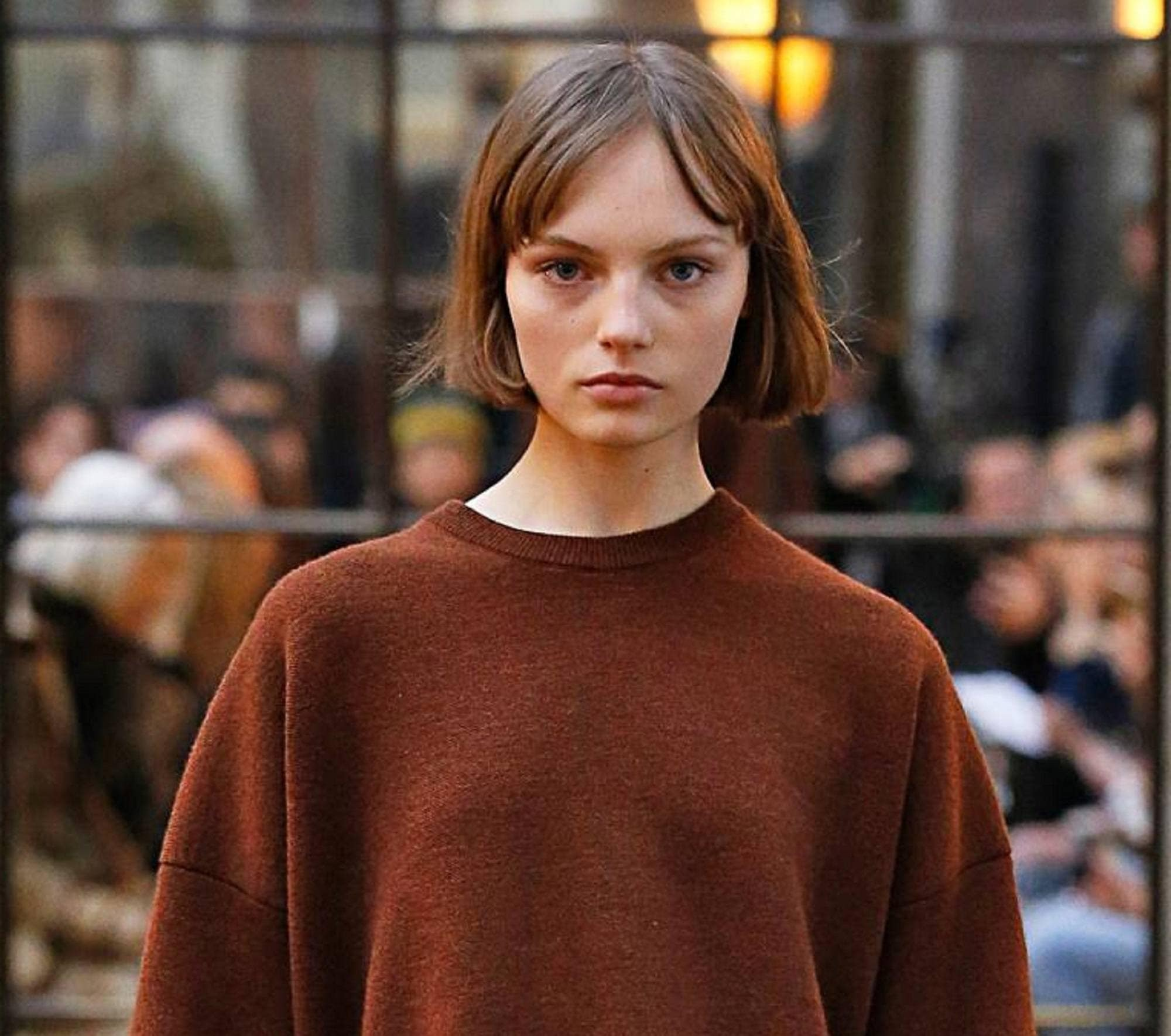 Chin length hairstyles: Runway shot of a woman wearing brown shirt with short brown center parted chin length bob