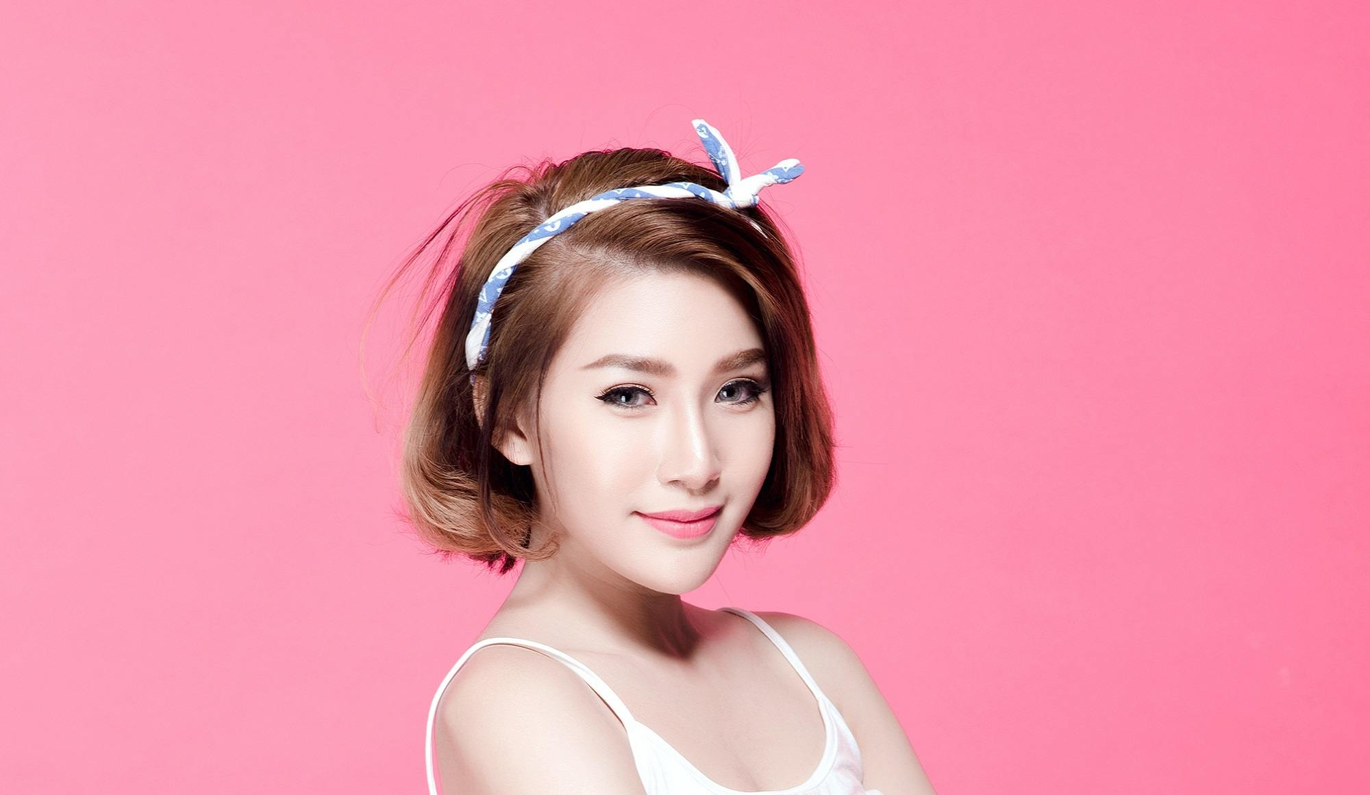 Chin length hairstyles: Closeup shot of Asian woman wearing white thin-strapped top with brown short hair and white headband standing against pink background
