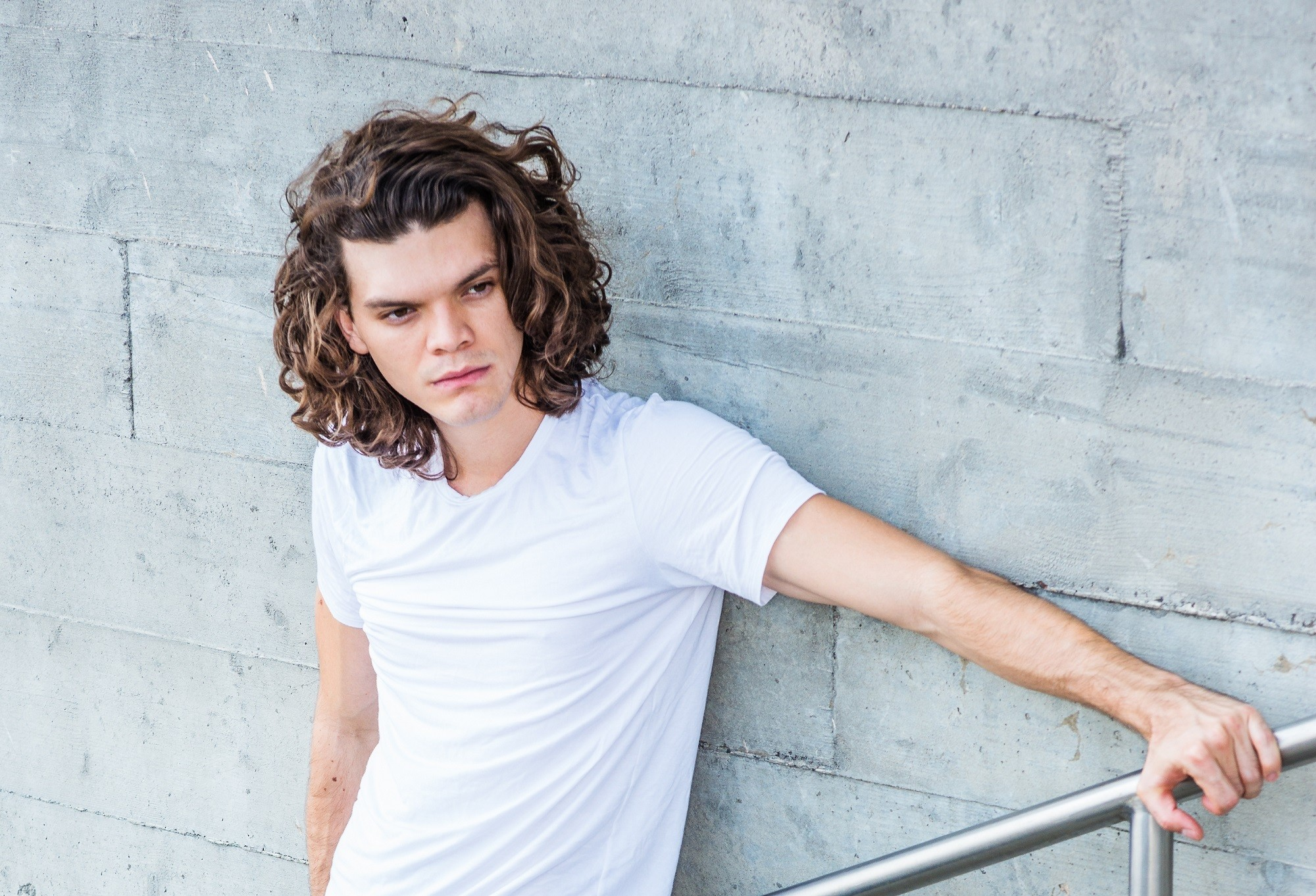 Curly hair men: Man in white shirt with medium-length curly brown hair standing against a gray wall outdors