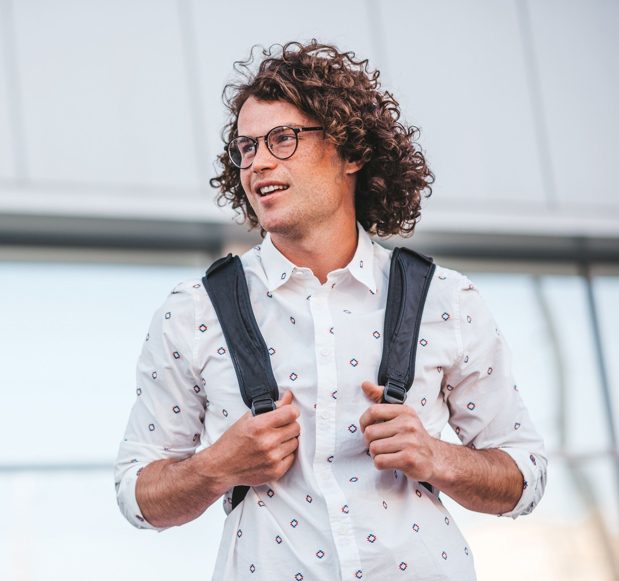 Curly hair main: Man carrying a backpack and wearing a white polo and eyeglasses with brown curly hair on an outdoor location