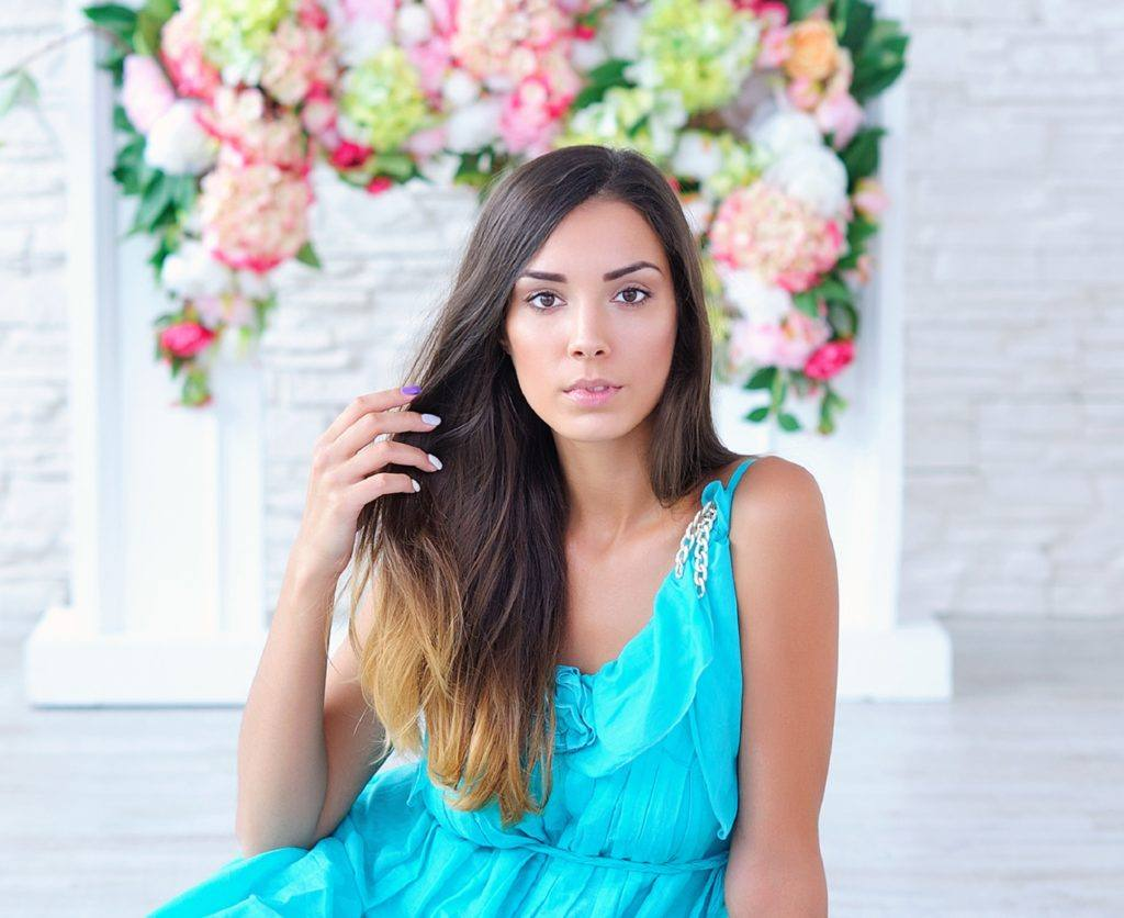 Dip dyed hair: Woman in blue dress with long black hair dip dyed in bronde sitting in front of floral background