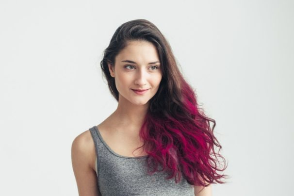 Dip dyed hair: Woman wearing a gray tank top with long curly dip dyed magenta hair standing against a white background