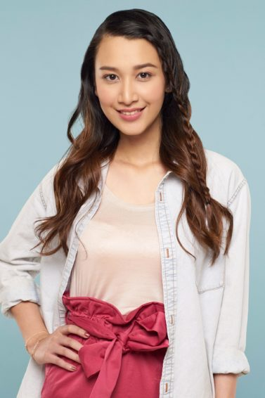 Face framing lace braid: Asian woman with long brown hair in lace braid wearing light peach blouse, white blazer, and pink skirt standing against a blue background with right and on hips