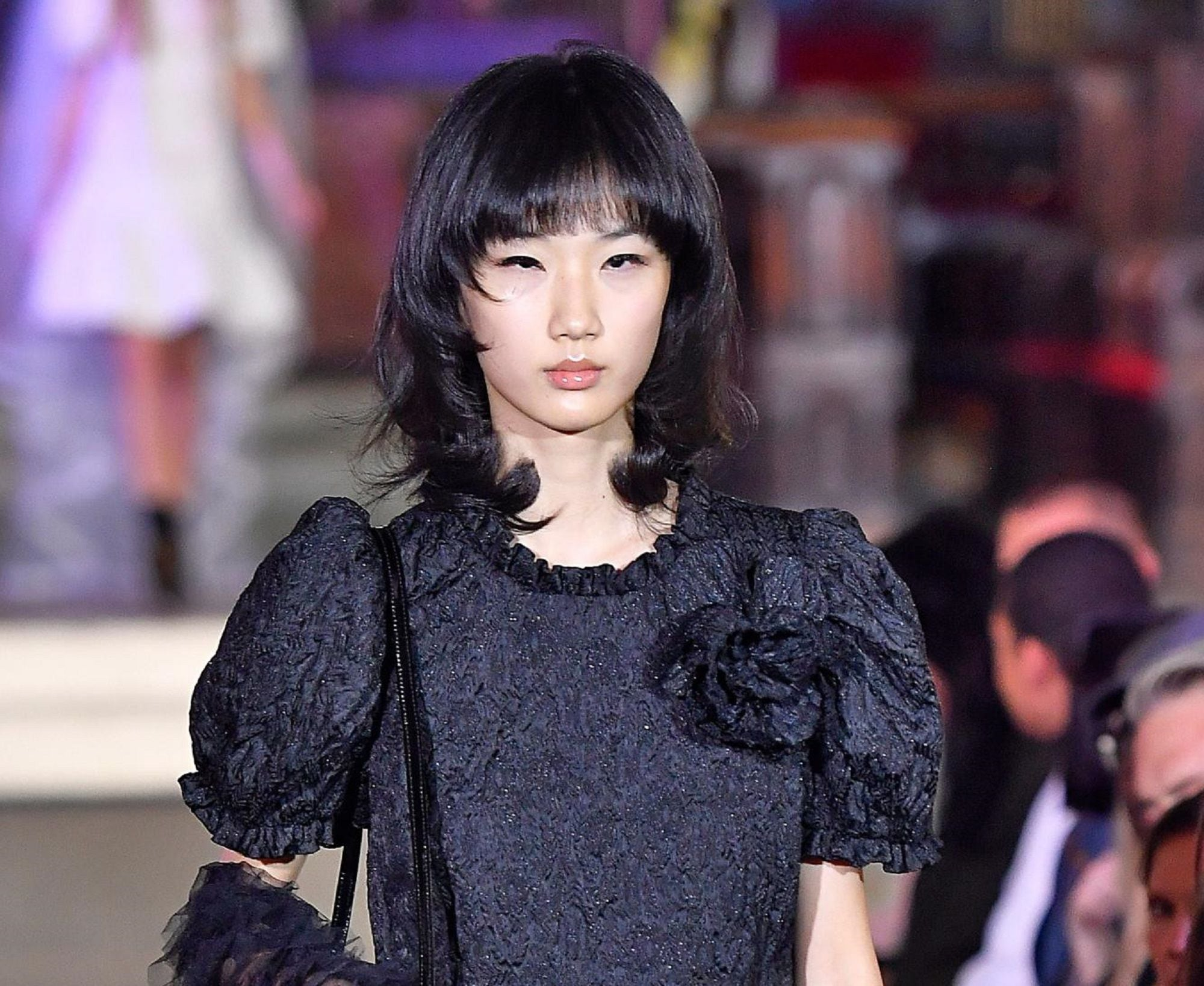 Goth hairstyles: Runway shot of Asian woman with black hair with bangs styled in goth hairstyle and wearing a dark gray dress