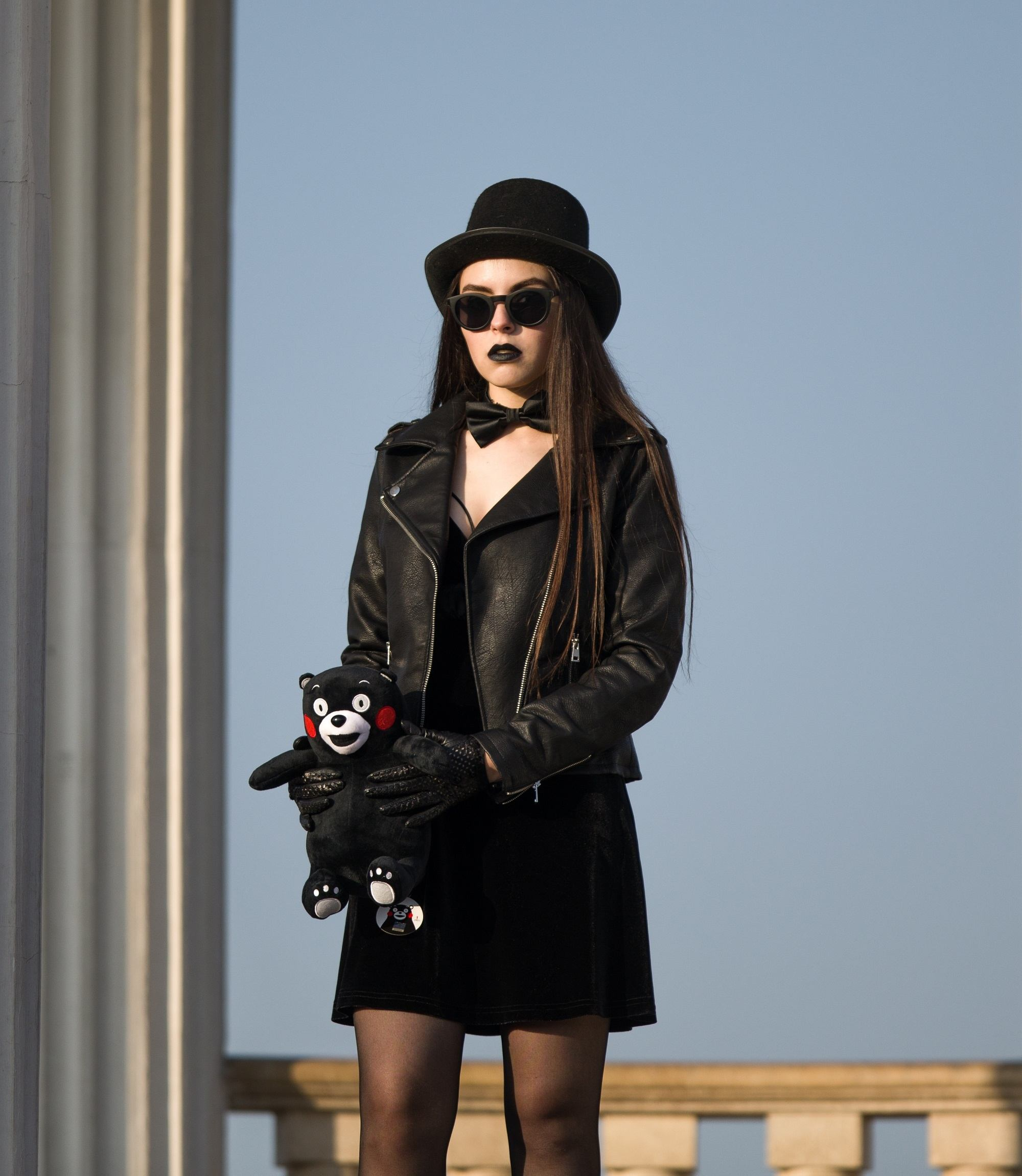 Goth hairstyles: Woman with long, straight dark brown hair wearing a hat, dark sunglasses, leather jacket and black dress and stockings in an outdoor location with blue sky at the background