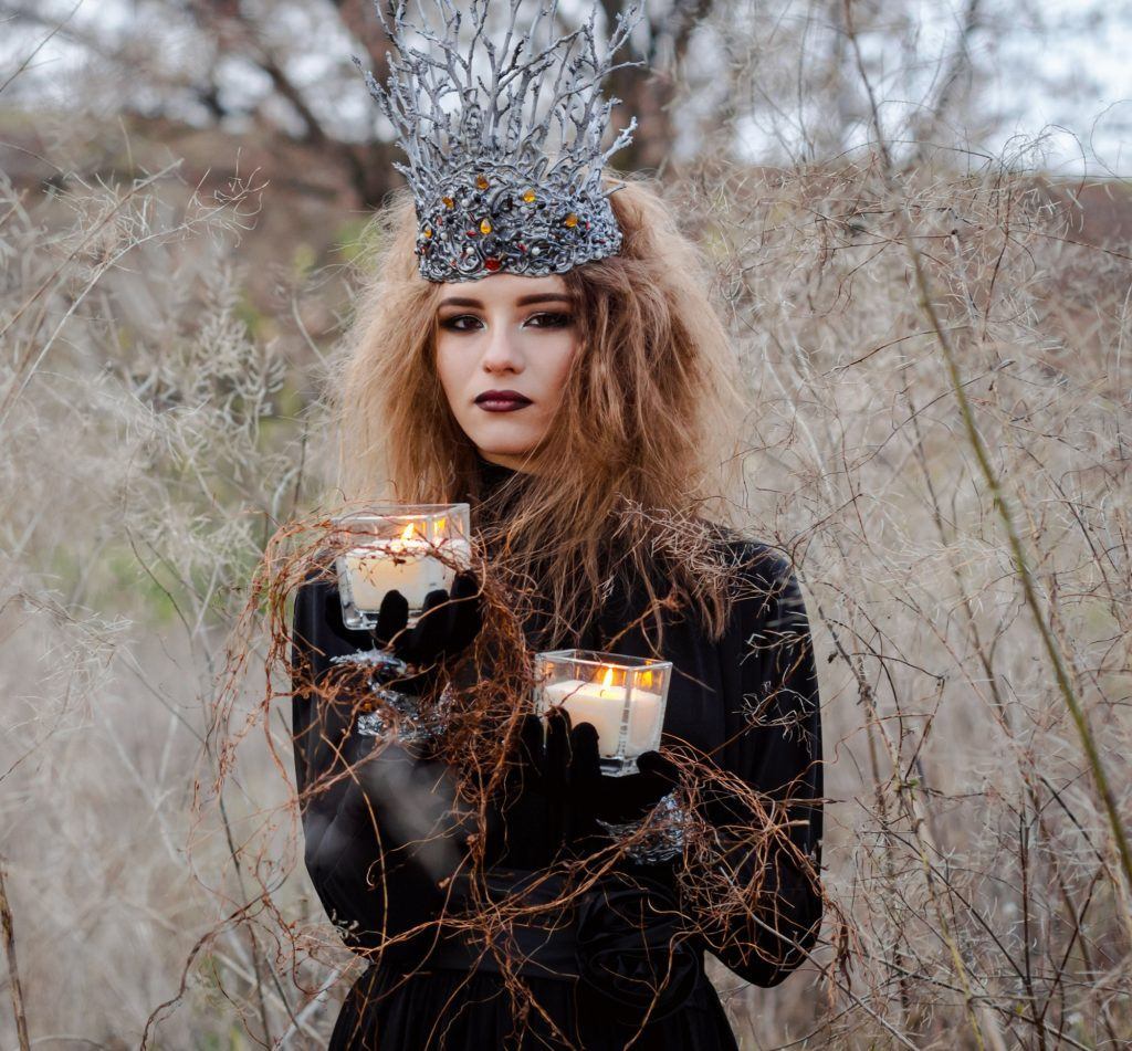 Goth hairstyles: Woman wearing long-sleeved black dress with long messy brown hair and big hairpiece in an outdoor location with dried grass