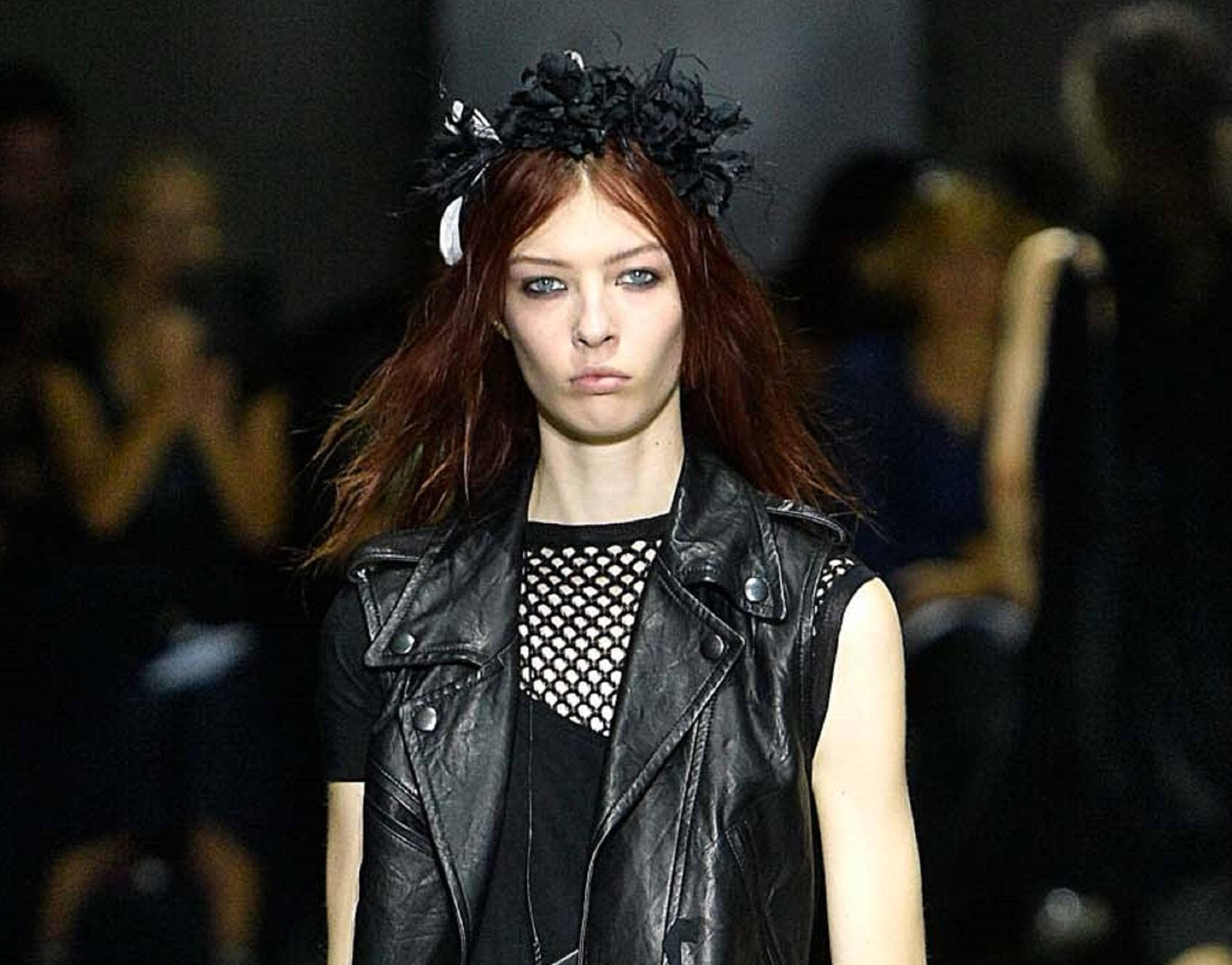 Goth hairstyles: Runway shot oman wearing black leather vest and black see-through top with reddish brown hair in a textured hairstyle topped with a black hair pece