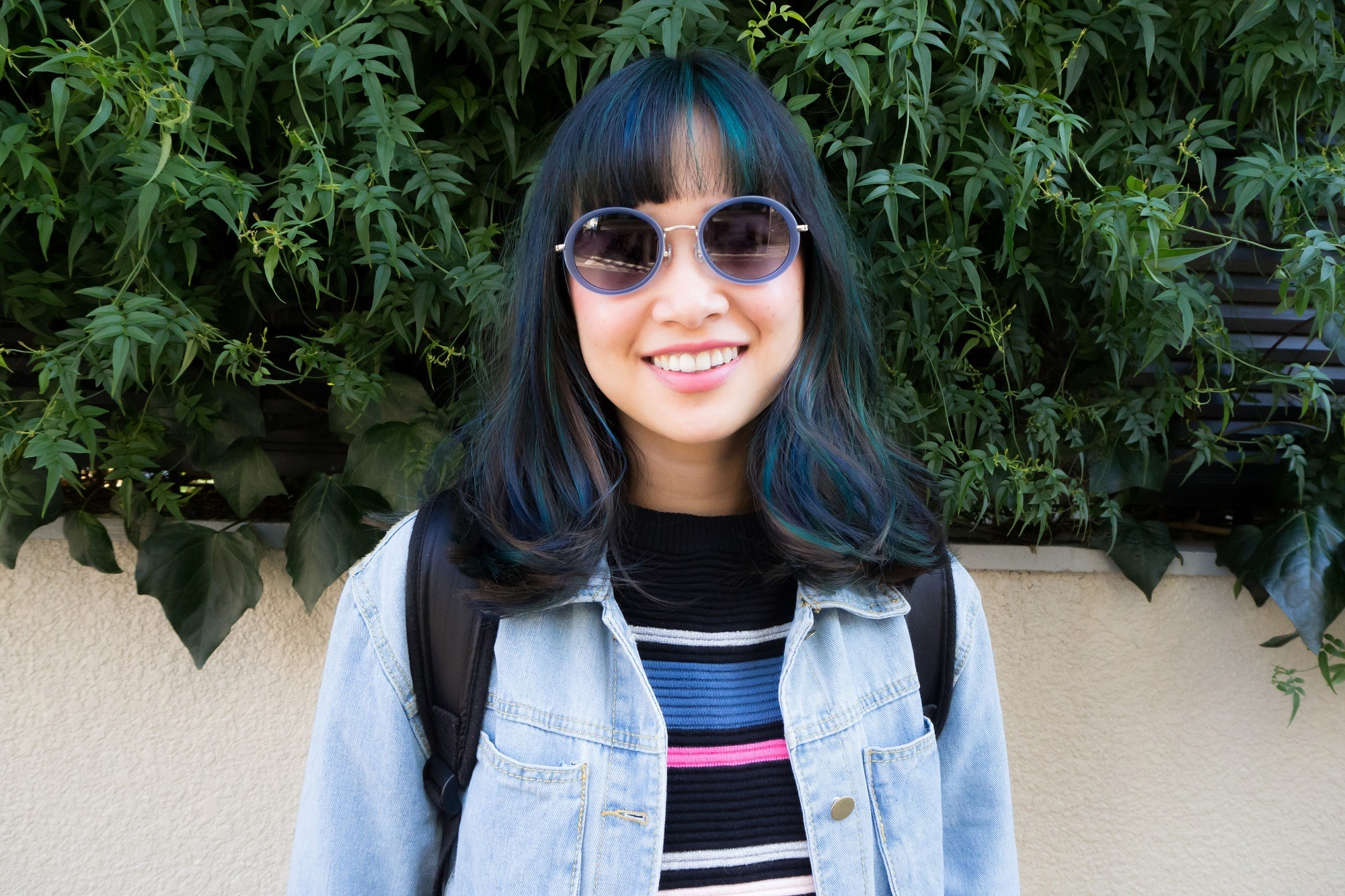Girl with shoulder-length hair with bangs and green hair streaks wearing striped shirt and jacket and shades standing against a leafy backdrop in an outdoor location