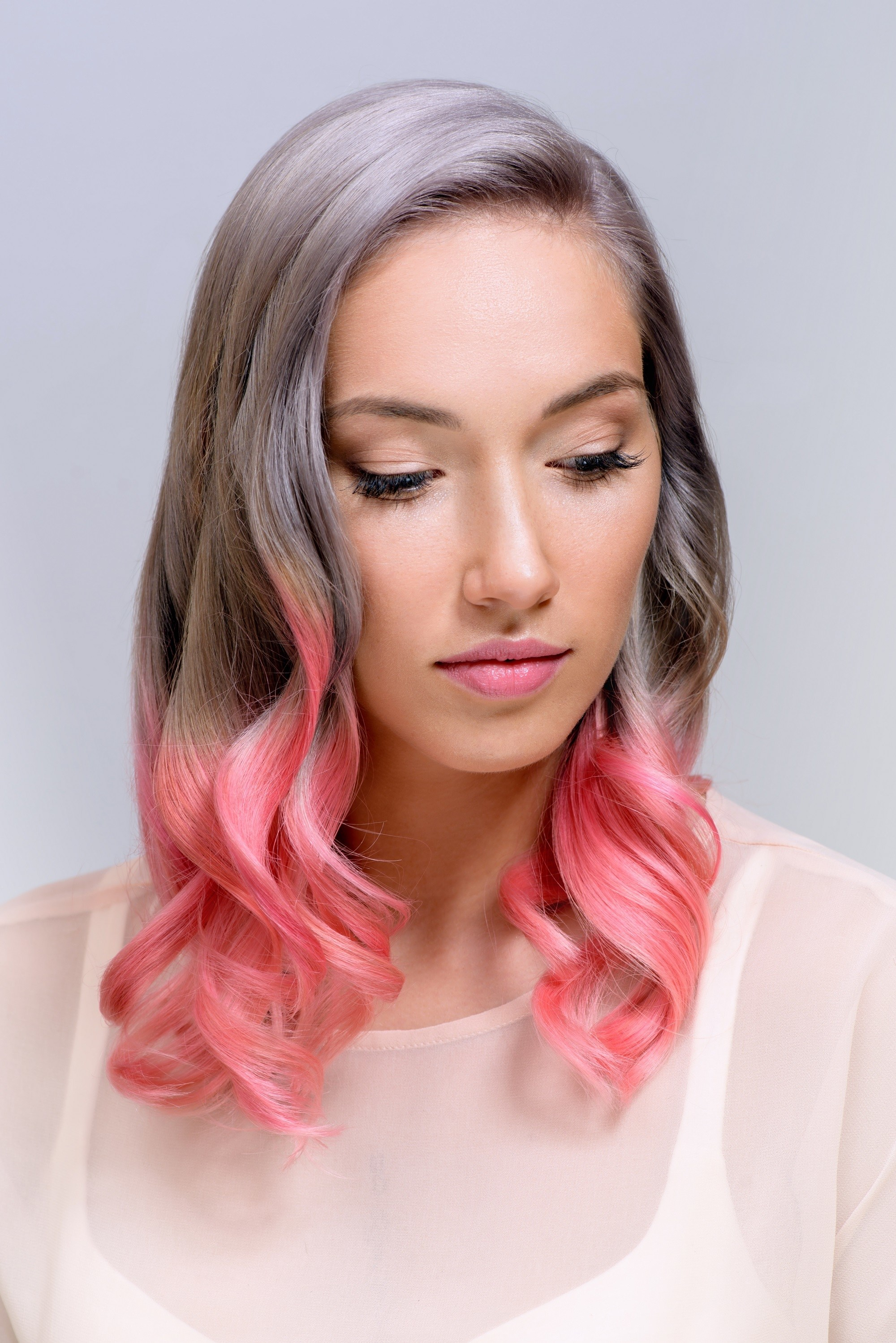 Woman with shoulder length wavy hair with pink hair streaks wearing white blouse closeup shot against gray background