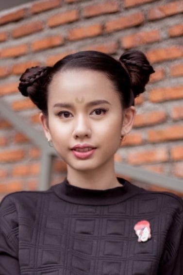 Asian girl with hair in Halloween glam double buns in outdoor location against a brick wall
